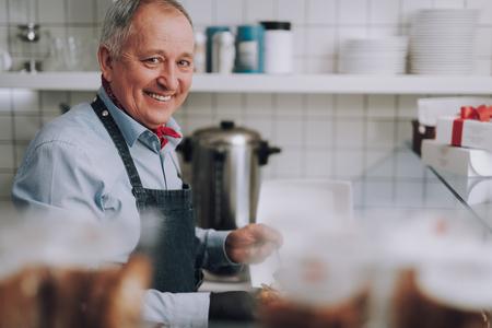Joyful senior man in apron working in his cafe
