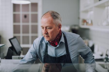 Elegant gentleman in apron standing behind the counter
