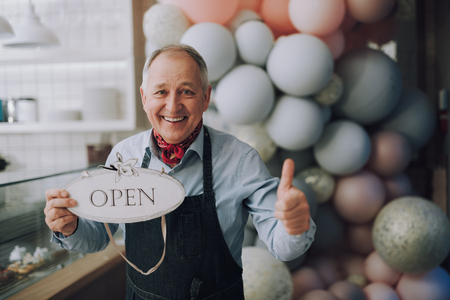 Happy small business owner holding open sign and showing thumbs up