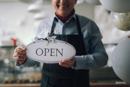 Joyful man in apron holding open sign with hand-drawn flowers