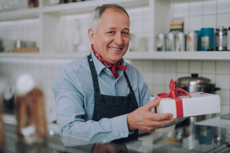 Joyful old man with present standing behind the counter Stok Fotoğraf