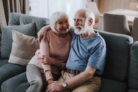 Happy elder couple embracing on sofa at home Banco de Imagens