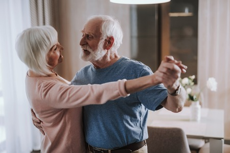Romantic elder couple dancing in living room
