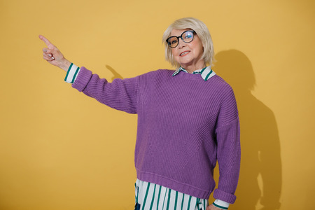 Fashionable elderly woman pointing index finger up against yellow background