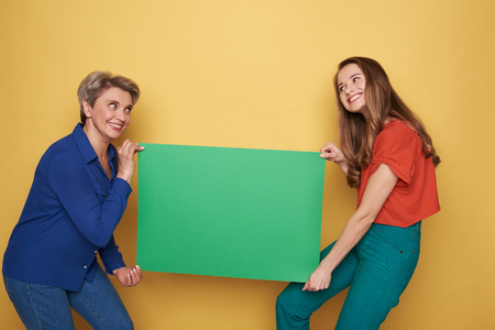 Cropped photo of Caucasian women holding green heavy empty poster in studio