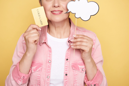 Cropped photo of Caucasian woman holding white paper cloud and gold card