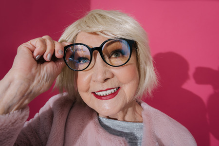 Portrait of fashionable smiling elderly woman touching her eyeglasses in studio Stok Fotoğraf