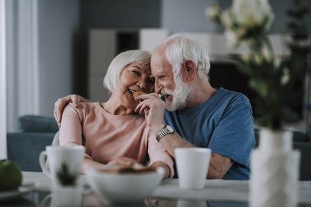Positive elder couple drinking tea with cookies