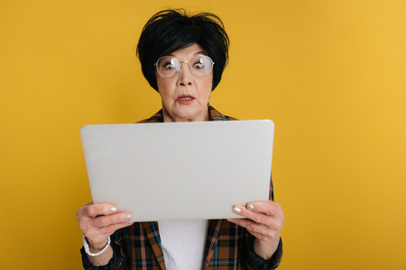 Surprised elderly lady is looking at screen of computer with big eyes