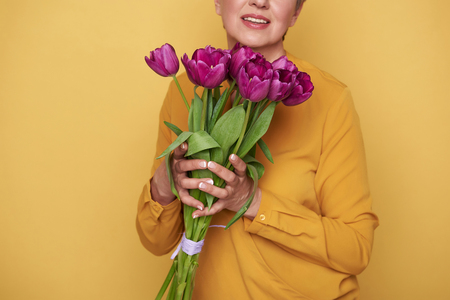 Cropped photo of Caucasian woman with cute bouquet of tulips in arms Standard-Bild - 119828011