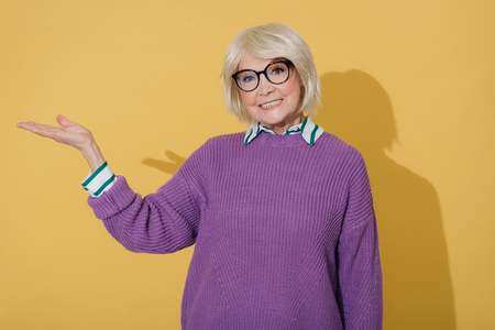 Cropped photo of happy stylish old lady gesticulating with arm in studio