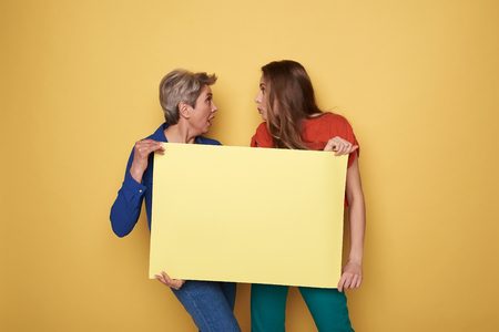 Cropped photo of surprised women holding yellow empty poster in studio
