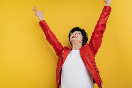 Low angle of smiling elderly woman wearing bright jacket on yellow background Reklamní fotografie
