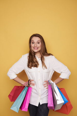 Waist up of Caucasian unconfident girl posing in studio with shopping bags