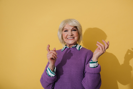 Waist up of happy elderly woman in purple sweater gesticulating with arms
