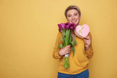 Waist up of smiling woman holding purple tulips and gift in arms Stock Photo