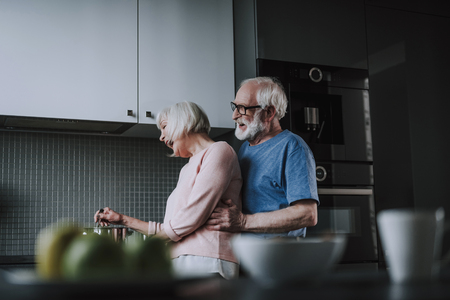 Happy senior couple cooking on kitchen at home