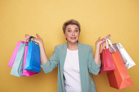 Surprised happy woman looking at camera with shopping bags in her arms Imagens