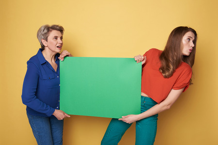 Cropped photo of Caucasian women holding green heavy empty poster in studio 版權商用圖片