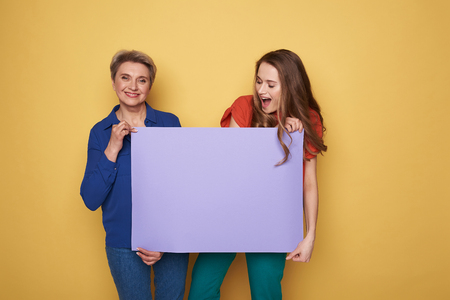Cropped photo of happy Caucasian women holding purple empty poster in studio
