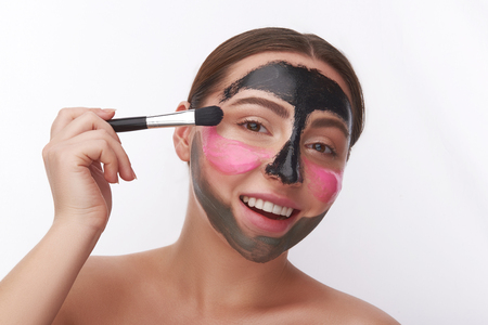 Excited woman opening her mouth while using facial masks