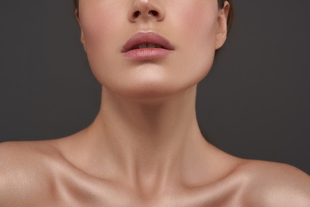 Schöne junge Frau mit perfekter Haut, die vor grauem Hintergrund steht Standard-Bild