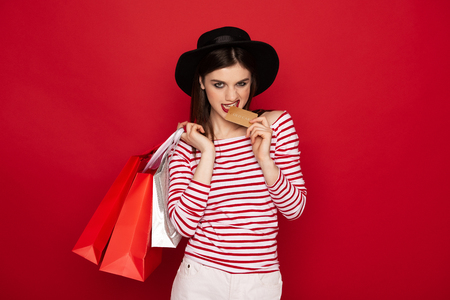 Confident lady with shopping packs and credit card