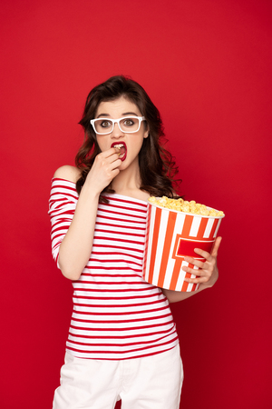 Bored pretty brunette lady eating pop corn