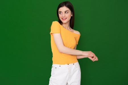 Coquettish young pretty girl isolated on green Stock Photo