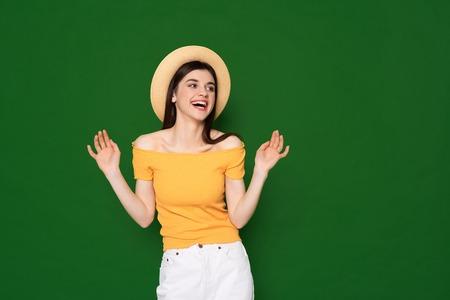 Joyful brunette cute girl isolated on green