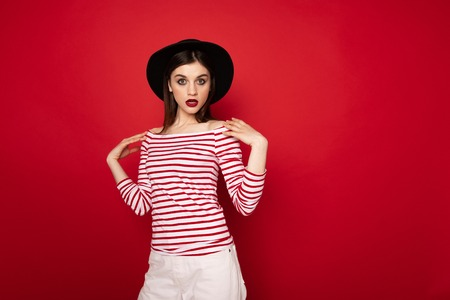 Surprised girl in striped blouse and black hat