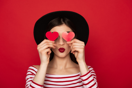 Coquettish girl closing eyes by red paper hearts