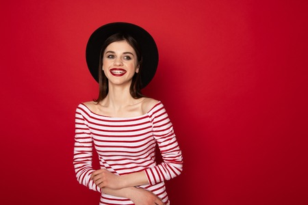Happy cute girl in striped blouse and black hat
