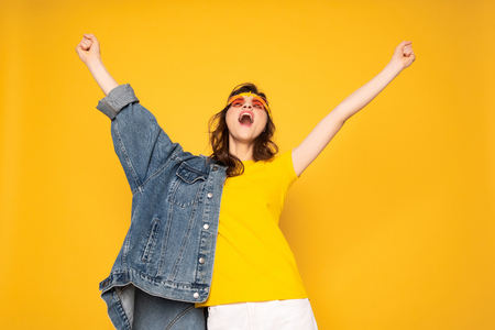 Happy screaming hipster girl holding hands up