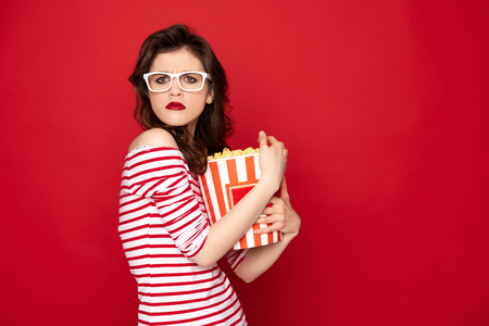 Greedy brunette lady grasping box with pop corn
