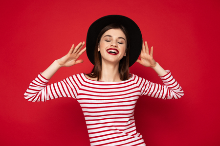 Joyful lady in striped blouse and black hat