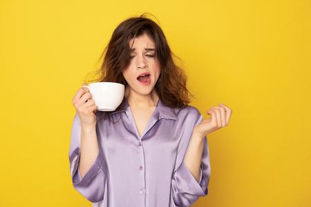 Jolie fille endormie avec une tasse de café le bâillement
