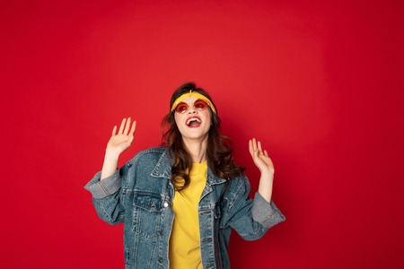 Happy smiling hipster girl isolated on red