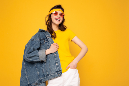 Cheerful hipster girl posing isolated on yellow