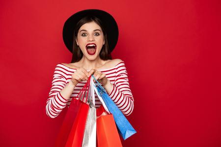 多くのショッピングパックを持つ幸せな叫び声の女性