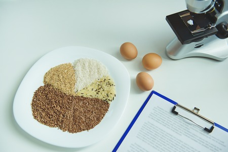 Modern microscope with eggs and cereal situating on laboratory table Stock Photo
