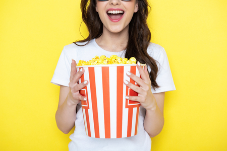 Cropped photo of happy brunette lady keeping bucket with popcorn