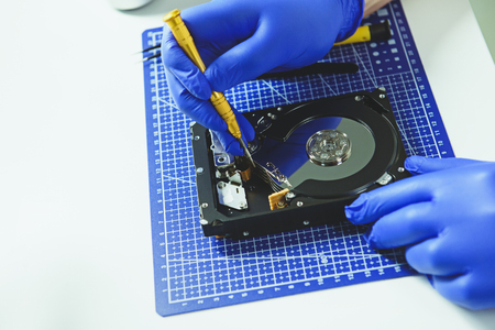 Engineer in protective gloves repairing computer HDD Imagens