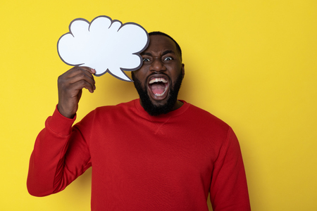 Waist up of African man holding speech bubble over head in studio Stock Photo - 121087379