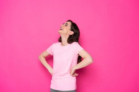 Side view of happy brunette Caucasian girl posing for camera in studio