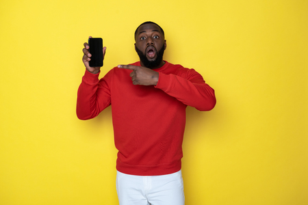 Waist up of surprised African man holding smartphone in arms Foto de archivo