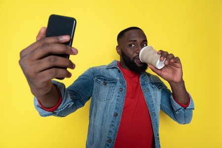 Waist up of handsome African man keeping cupholder and smartphone in arms Banco de Imagens