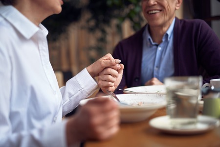 Man and woman holding hands sitting in cafe