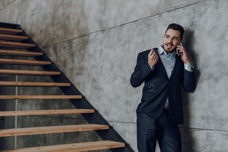 Relaxed businessman is talking on phone near stairwell