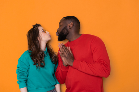 Half length portrait of happy interracial couple in studio
